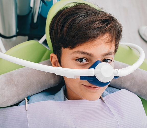 Young boy with nitrous oxidesedation dentistry mask in place