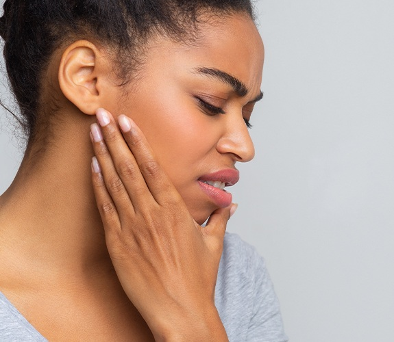 Woman in need of T M J treatment holding jaw in pain